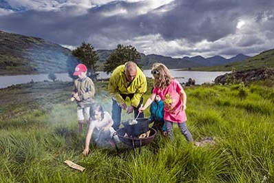 children cooking on a fire with a loch side background